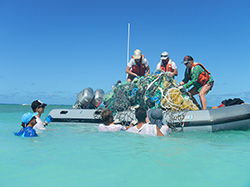 The Marine Debris Team loads a small boat with derelict fishing gear at Lisianski Island.