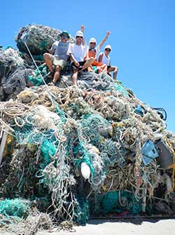 Participants of marine debris removal activities sit atop a mound of derelict fishing gear collected in Papahānaumokuākea Marine National Monument.