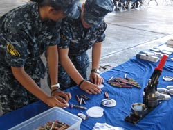 U.S. Naval Officers making buttons at the Papahānaumokuākea outreach table.
