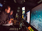 Expedition science leads Christopher Kelley (background) and Daniel Wagner (foreground) monitor an ROV dive in the science control room of the <em>Okeanos Explorer</em>.