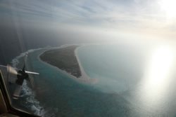 A U.S. Coast Guard C-130 flys over Kure Atoll-Green Island during a tsunami damage assessment flight.