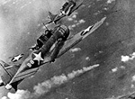 SBD Dauntless dive bombers approaching the burning Japanese heavy cruiser Mikuma.