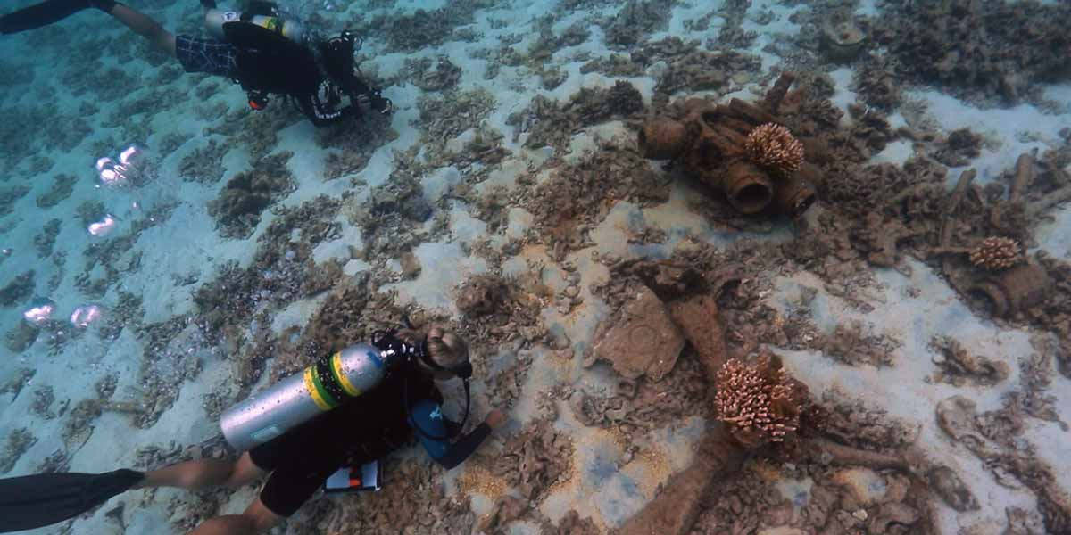 NOAA maritime archaeologists survey the remains of a sunken World War II era aircraft at Midway Atoll.