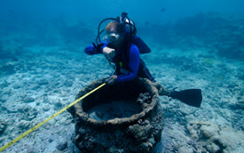 Maritime archaeologist Jason Raupp surveys a trypot at the <i>Two Brothers</i> site.